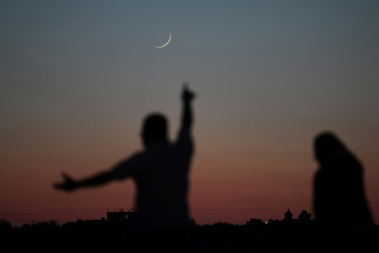 A Palestinian man points towards the crescent moon in Khan Yunis in the southern Gaza Strip on May 16, 2018, a day before the start of the Muslim holy month of Ramadan. (Photo:AFP/Said Khatib)
