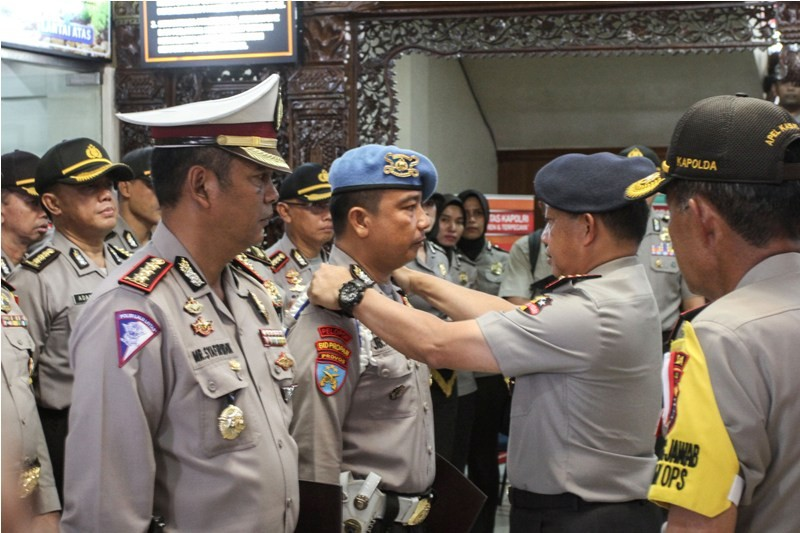 Kapolri Jenderal Pol Tito Karnavian (kedua kanan) menyematkan tanda kenaikan pangkat kepada Anggota Provost Polda Riau Aipda JB Panjaitan saat upacara kenaikan pangkat luar biasa di Mapolda Riau, di Pekanbaru, Riau, Kamis (17/5). Antara