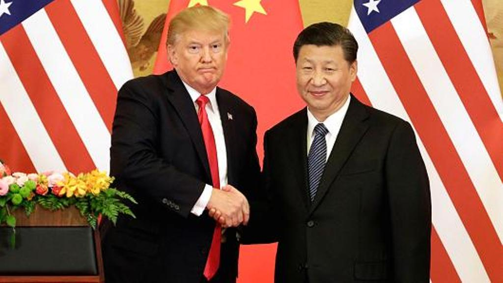 Presiden AS Donald Trump (kiri) berjabat tangan dengan Presiden Tiongkok Xi Jinping (Qilai Shen/Bloomberg)
