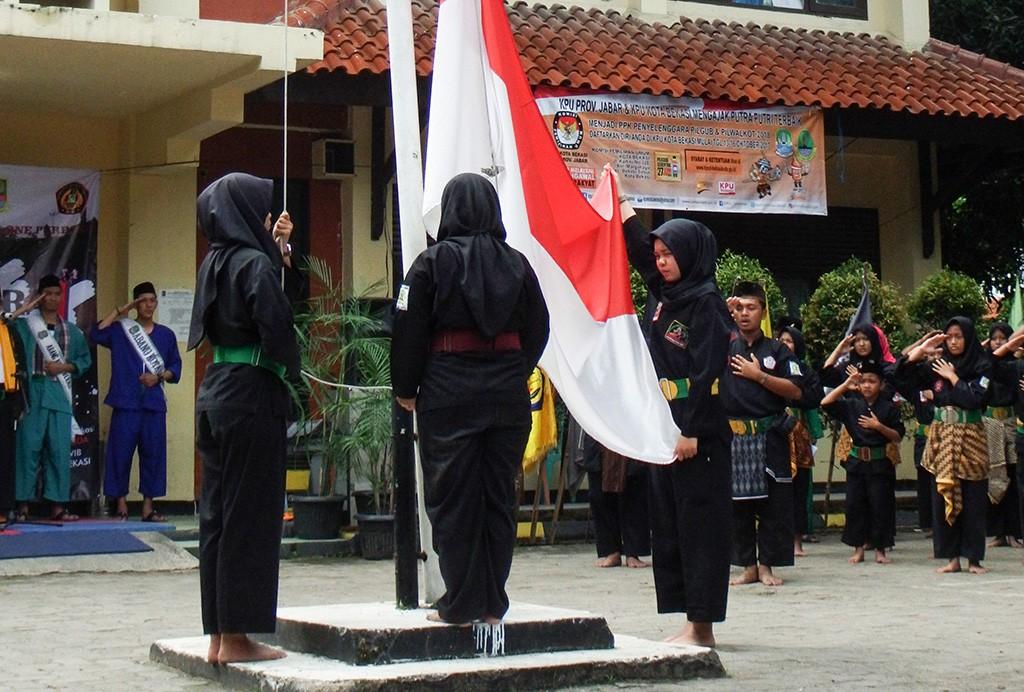Petugas pengibar bendera beraksi pada upacara peringatan hari Sumpah Pemuda ala Pencak Silat.  Foto: Antara/Paramayuda