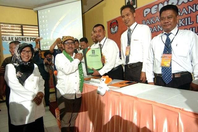 Ummi Azizah (kiri) saat bersama Enthus Susmono (kanan) enyerahkan berkas pendaftaran kepada Ketua KPU Kabupaten Tegal, Sukartono (ketiga kanan) saat mendaftar di KPU Kabupaten Tegal, Jawa Tengah, Rabu (10/1). Foto: Oky Lukmansyah/Antara