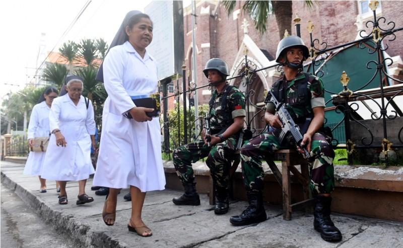 Petugas keamanan berjaga di depan gereja saat misa di Gereja Katolik Kelahiran Santa Perawan Maria, Surabaya, Jawa Timur, Minggu (20/5).