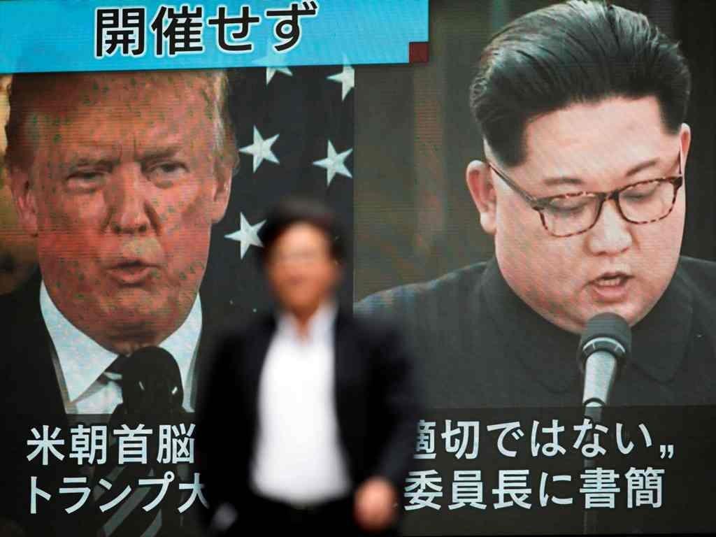Seorang pejalan kaki berjalan di depan layar di Tokyo dengan menampilkan laporan berita yang berkaitan dengan Presiden AS Donald Trump yang membatalkan pertemuannya dengan pemimpin Korea Utara Kim Jong Un. (Foto: AFP/Behrouz Mehri).