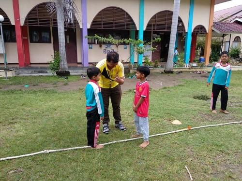 Seorang Guru sedang membimbing kegiatan siswa di luar kelas.