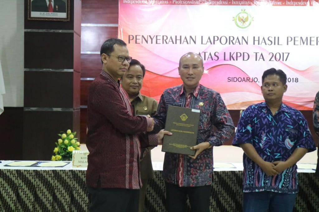 Pjs Walikota Malang Wahid Wahyudi (batik merah) menghadiri penyerahan LHP atas LKPD ini berlangsung di Kantor BPK perwakilan Provinsi Jawa Timur. Medcom.id/Daviq Umar Al Faruq