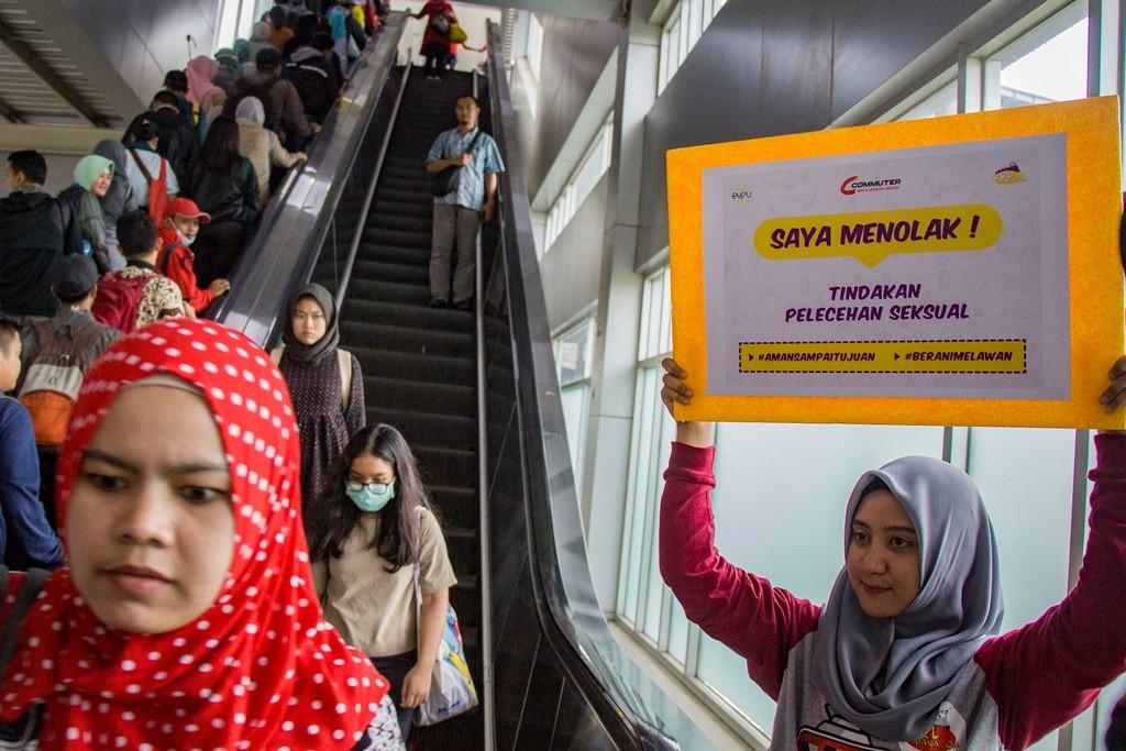 Relawan mengangkat poster ajakan untuk mencegah pelecehan seksual di Stasiun Tanah Abang, Jakarta. (Foto: ANTARA/Galih Pradipta)