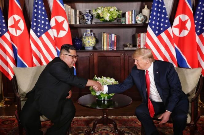 Kim Jong-un (kiri) dan Donald Trump (kanan) saat melakukan pertemuan untuk pertama kalinya. (FOTO: AFP)