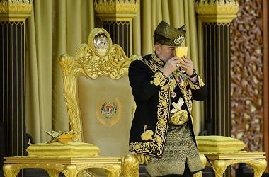 Raja Malaysia Sultan Muhammad V mencium sebuah Al-Quran di