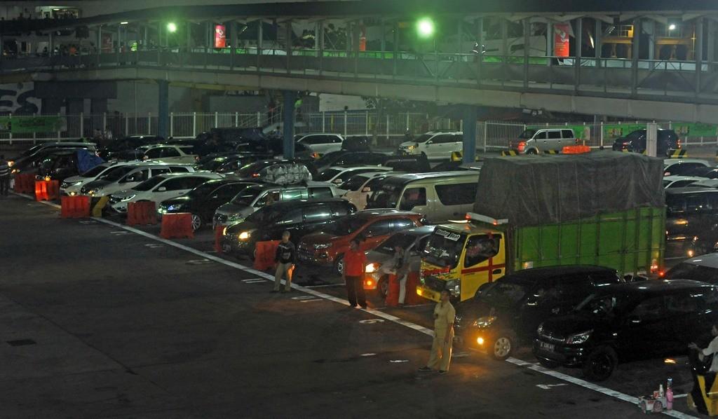 : Sejumlah petugas mengatur antrean kendaraan roda empat yang akan masuk kapal ferry di Pelabuhan Merak Banten. Antara