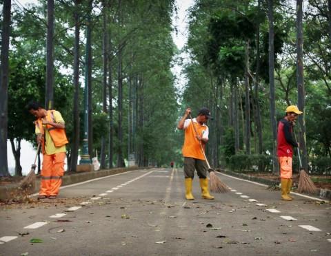 Sejumlah petugas dari Suku Dinas Kebersihan menyapu jalan