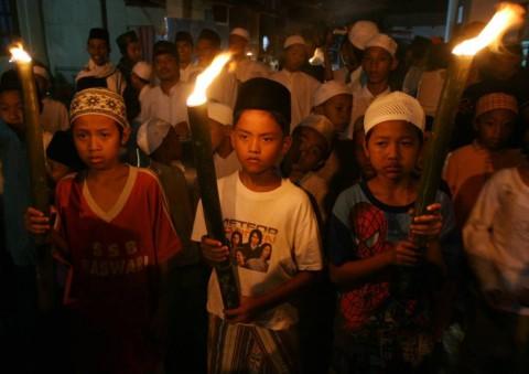 Tiga anak membawa obor yang diiringi oleh ratusan warga lainnya