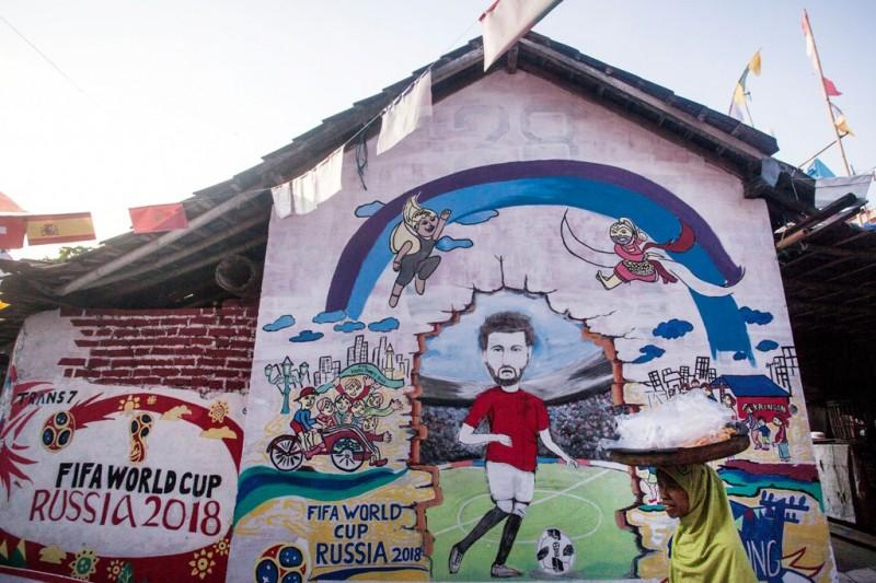Warga melintas di areal kampung yang didekorasi dengan nuansa Piala Dunia 2018 di Tegalrejo, Yogyakarta. (Foto: Antara/Andreas Fitri Atmoko).