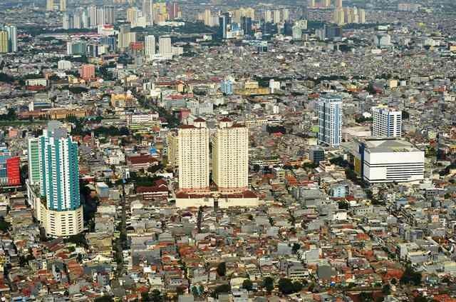 Bangunan gedung apartemen di antara pemukiman padat di salah satu sudut Jakarta. AFP Photo/Adek Berry