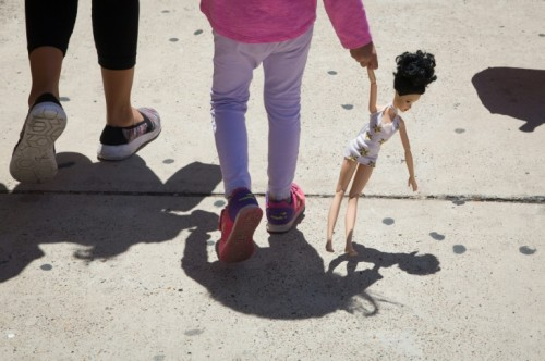 A 4-year-old Honduran girl carries a doll while walking with her
