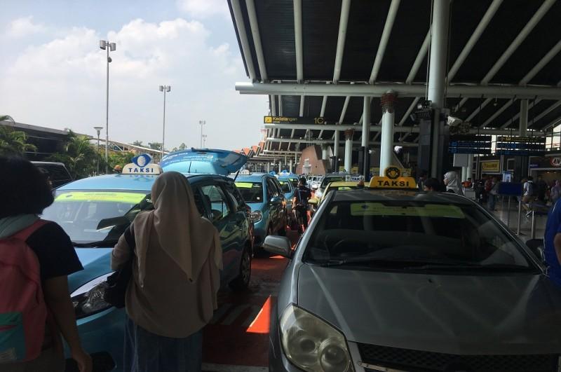 Suasana penumpang mengantre taksi di depan Terminal 1 Kedatangan Bandara Soekarno-Hatta Tangerang, Selasa 19 Juni 2018, Medcom.id - Farhan Dwi