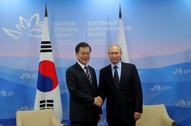 Presiden Korsel Moon Jae-in (kiri) berjabat tangan dengan