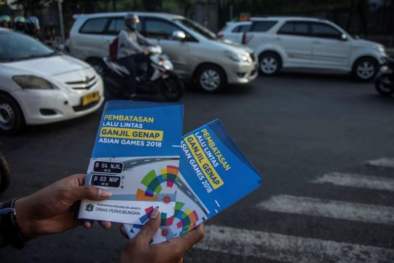 Petugas Badan Pengelola Transportasi Jabodetabek (BPTJ) melakukan sosialisasi kepada pengguna kendaraan bermotor pada hari pertama uji coba perluasan kawasan ganjil genap di persimpangan Pancoran, Jakarta, Senin (2/7). ANTARA FOTO/Aprillio Akbar.