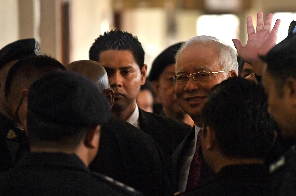 Mantan PM Malaysia Najib Razak melambaikan tangan saat hendak ditransfer ke pengadilan tinggi usai hadir di kompleks pengadilan Duta di Kuala Lumpur, 4 Juli 2018. (Foto: AFP/MOHD RASFAN)
