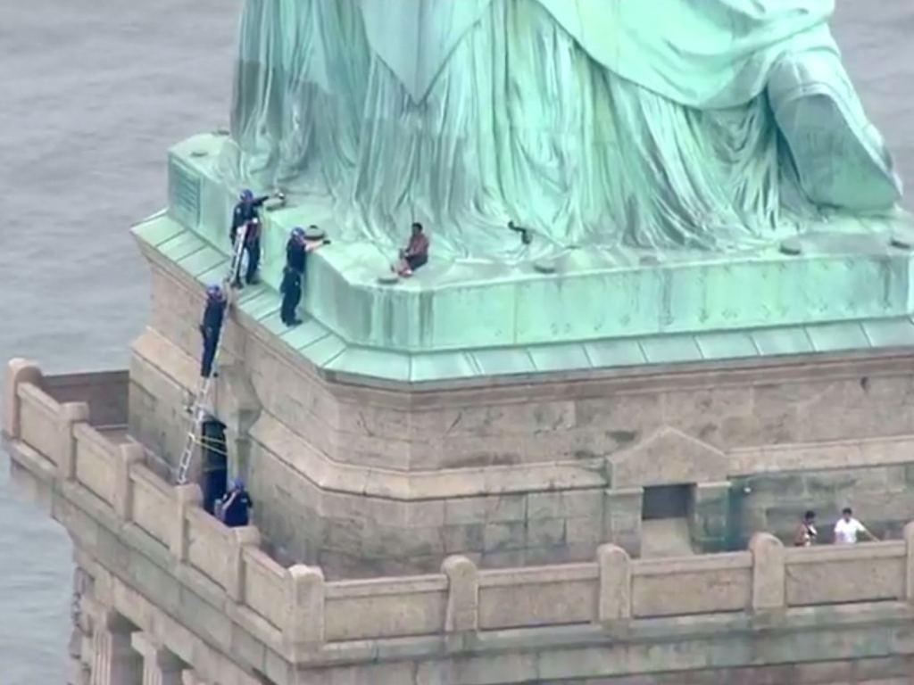 Polisi menyelamatkan wanita yang panjat Patung Liberty. (Foto: AFP).