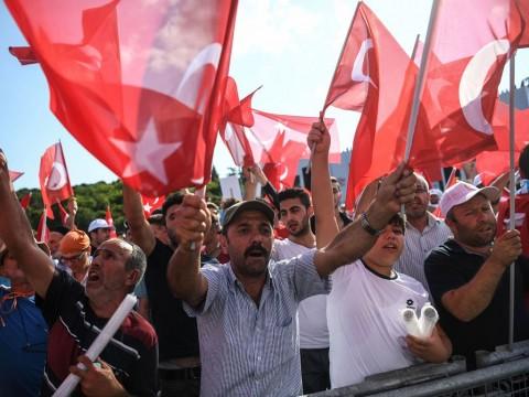 Warga Turki melambaikan bendera di atas Jembatan Bosphorus.