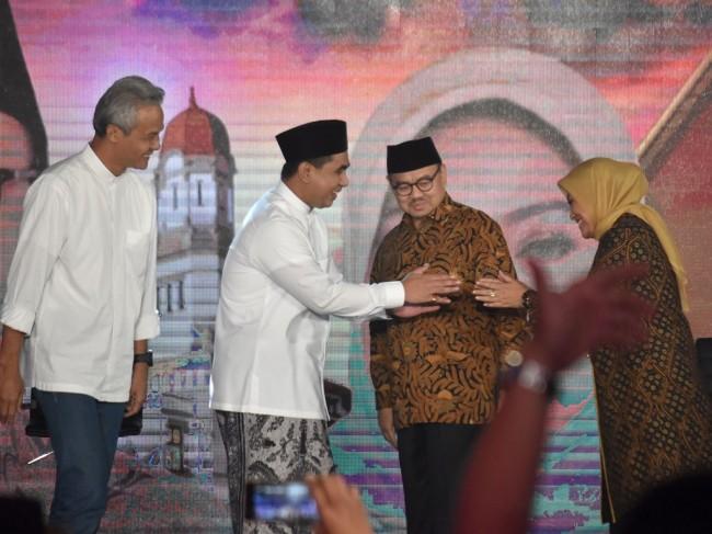 Calon gubernur Ganjar Pranowo (kiri) dan Sudirman Said (kedua kanan) menyaksikan calon wakil gubernur Taj Yasin (kedua kiri) dan Ida Fauzia (kanan) berjabat tangan saat Debat Terbuka Pilkada Jawa Tengah di Ballroom Hotel Patra, Semarang, Jawa Tengah