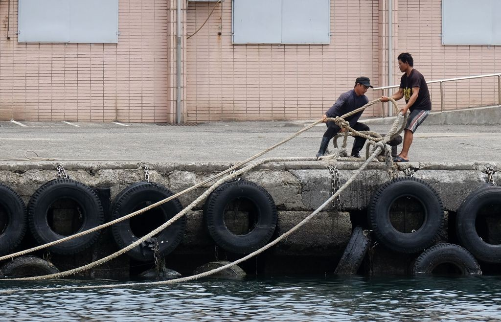 Para nelayan menarik kapalnya agar tak terdampak badai. (Foto: AFP)