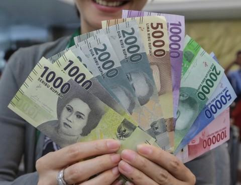 Seorang nasabah menunjukkan uang kertas rupiah baru tahun emisi