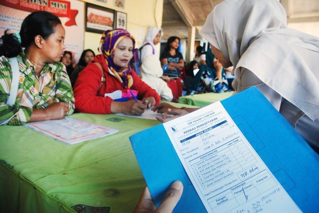Guru memeriksa berkas murid baru saat daftar ulang Penerimaan Peserta Didik Baru (PPDB) di SMPN 1 Cimenyan, Kabupaten Bandung, Jawa Barat. (Foto: ANTARA/Heru Salim)