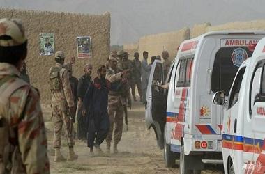 Personel militer dan warga berkumpul dekat ambulans yang