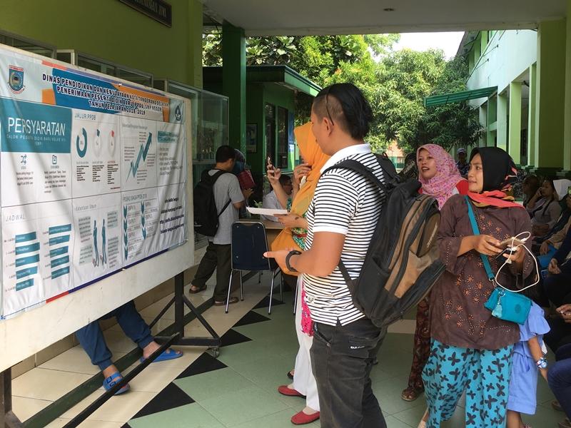 Orang tua calon siswa sedang membaca informasi pendafataran peserta didik baru (PPDB) Online SMA/SMK, Kamis, 21 Juni 2018. Medcom.id/Farhan Dwitama