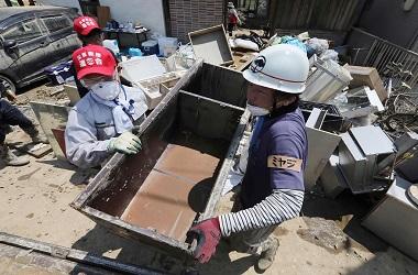 Petugas membersihkan puing dari area terdampak banjir di