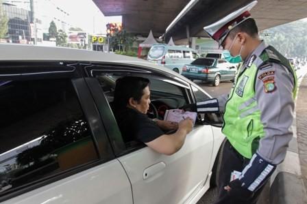 Pengemudi kendaraan roda empat menandatangani surat tilang setelah terbukti melanggar aturan perluasan pembatasan kendaraan sistem ganjil genap di simpang empat Slipi. Foto: MI/Pius Erlangga.