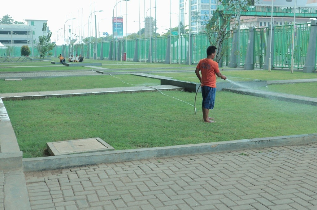Seorang petugas tengah menyiram taman di bagian depan Stadion Patriot Candrabaga, Kota Bekasi, Medcom.id - Antonio