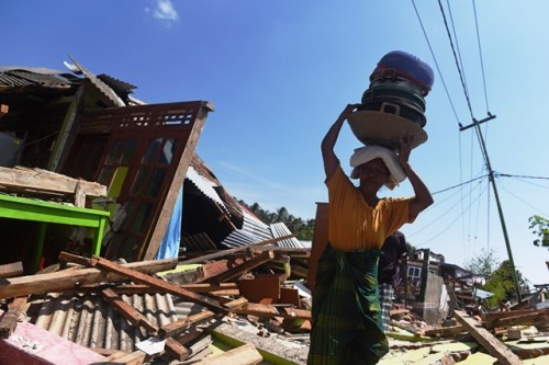 Seorang warga memungut perkakas dapur dari puing-puing rumahnya