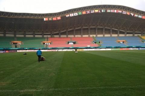 Pekerja membersihkan lapangan di Stadion Patriot Candrabaga,
