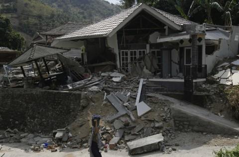 Warga mencari barang berharga miliknya di antara reruntuhan