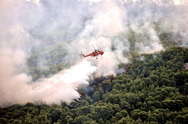 Helikopter menyiramkan air ke area kebakaran hutan di desa