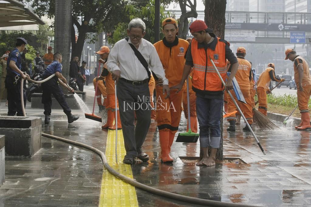 Petugas PPSU dan Damkar Bersihkan Trotoar Sambut Asian Games
