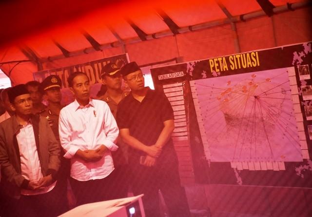 Presiden Jokowi diapit Gubernur NTB TGB Zainul Majdi dan Gubernur NTB Terpilih Zulkieflimansyah (kanan) menyimak paparan BNPB tentang wilayah terdampak gempa di Posko Utama Pengungsian Tanjung, Lombok Utara, Senin (13/8/2018). Antara Foto/Ahmad Subaidi