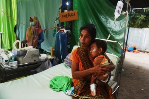 Seorang ibu memangku putranya di bangsal rumah sakit lapangan di