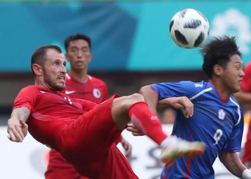 Pesepak bola Hong Kong Fernando Comi Recio (kiri) menghalau