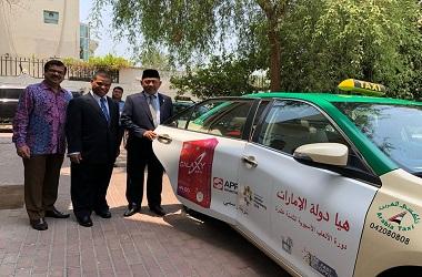 Dubes Husni berada di samping mobil taksi yang terpasang logo