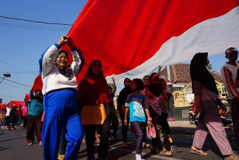 Warga membentangkan bendera sepanjang 350 menter di Jombang. Medcom.id/Nurul Hidayat