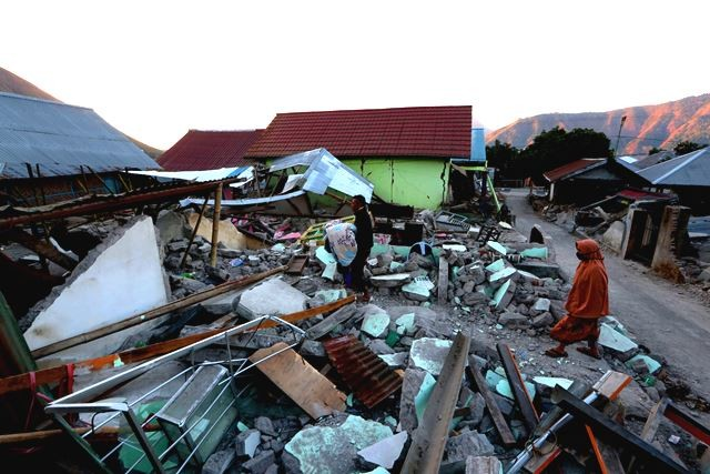 Warga korban gempa di Sembalun mencari barang-barangnya yang bisa diselamatkan di antara puing-puing rumahnya.. AFP Photo