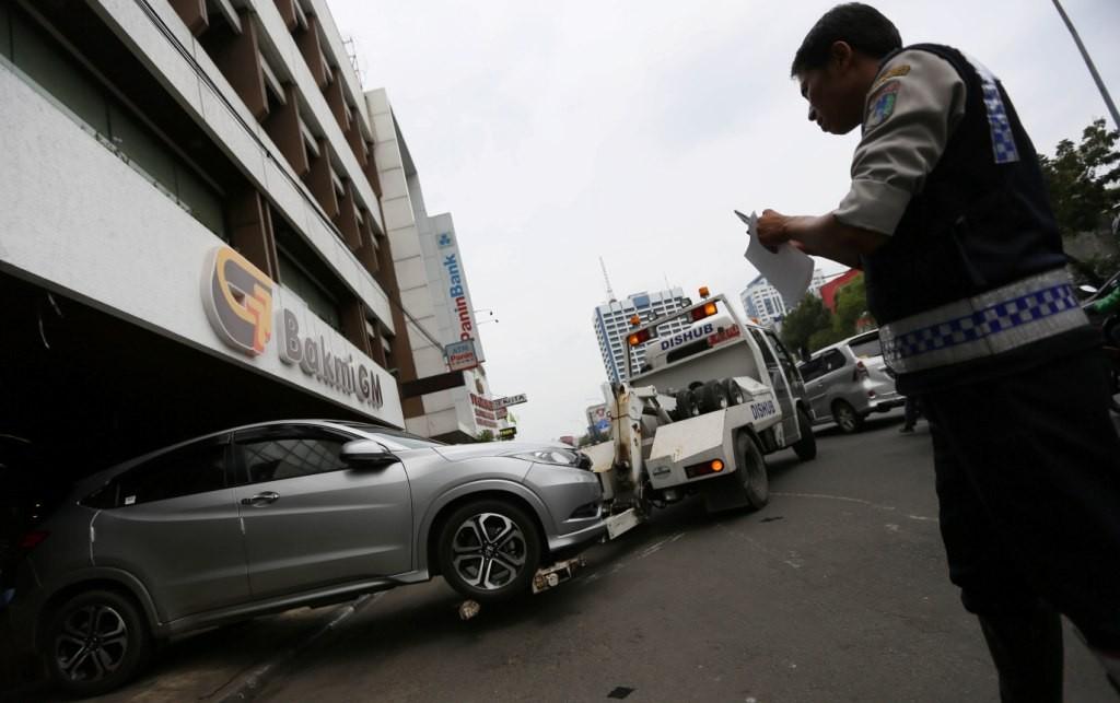 Petugas Dinas Perhubungan Jakarta Pusat menderek mobil yang parkir liar di jalan Gajah Mada, Jakarta. Foto: MI/Ramdani.