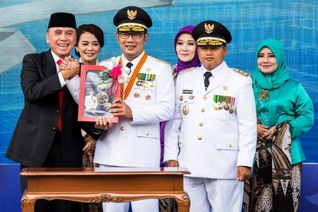 Gubernur Jawa Barat Ridwan Kamil (tengah) didampingi Wakil Gubernur UU Ruzhanul Ulum (kedua kanan) menerima buku laporan dari Penjabat Gubernur Jabar M Iriawan (kiri) saat acara Sertijab Gubernur Jawa Barat di Gedung Sate, Bandung, Jawa Barat, Kamis (6/9)