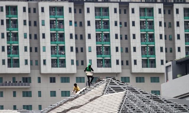 Dua pekerja menyelesaikan pemasangan atap bangunan dengan latar belakar gedung apartemen di Surakarta. Kebutuhan tenaga bidang bangunan tergolong tinggi, bahkan hingga ke pemukiman. Antara Foto/M Ayudha