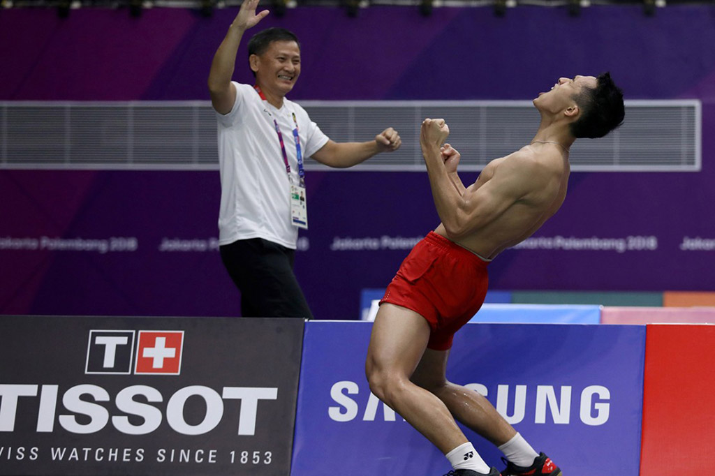 Selebrasi Jonatan Christie (kanan) dan pelatih Henry Saputra (kiri) usai menundukkan pebulu tangkis Jepang Kenta Nishimoto, pada pertandingan babak semifinal nomor perorangan Asian Games 2018 di Istora Senayan. Antara Foto/INASGOC/Nafielah Mahmudah