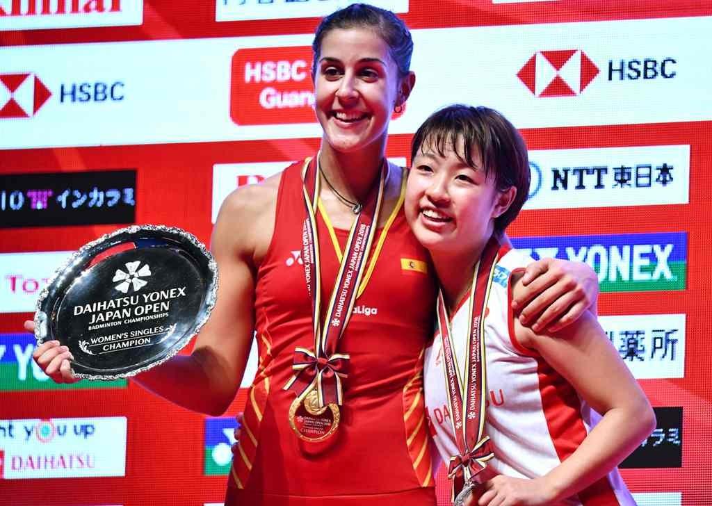 Carolina Marin (kiri) berpose di podium dengan Nozomi Okuhara usai memenangi gelar juara tunggal putri Japan Open 2018 (Kazuhiro NOGI / AFP)