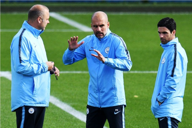 Mikel Arteta (kanan) berdiskusi dengan staf pelatih Manchester City di sesi latihan tim. (Foto: Oli SCARFF / AFP)